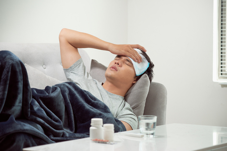 sick wasted man lying in sofa suffering cold and winter flu virus having medicine tablets in health care concept looking temperature on thermometer Standard-Bild