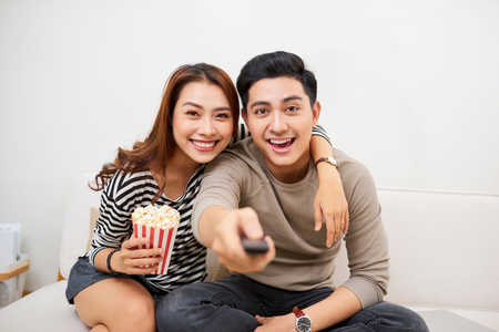 Young couple watching tv, eating pop-corn and having fun together.