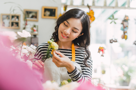 Happy beautiful young woman florist  standing in flower shop