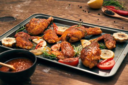 Grilled chicken drumstick and wings on baking tray over wooden table