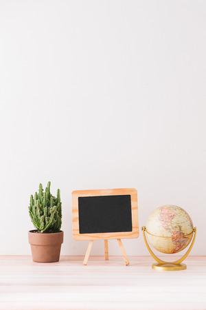Mockup blackboard frame, globe, cactus on well arranged desk.