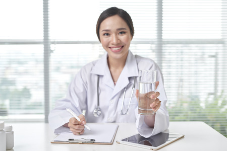 Smiling Female Doctor offering a glass of water in her Office Banco de Imagens
