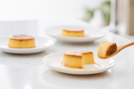 A bite piece of sweet creamy caramel custard in spoon and in plate
