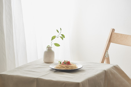 Food, spaghetti bolognese sauce in white dish and a vase of plants on a white prepared table