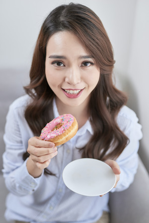 Portrait of beautiful young woman eating donuts at home. Stok Fotoğraf