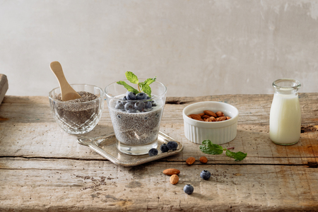 Healthy breakfast or morning snack with chia seeds pudding and berries on wooden rustic background, vegetarian food, diet and health concept