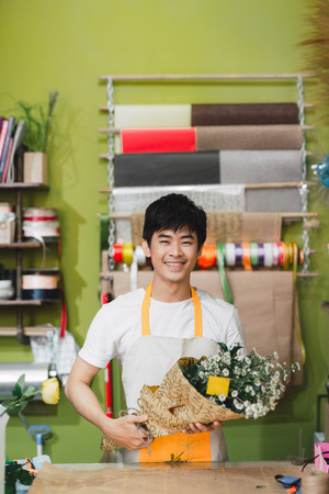 Ho Chi Minh City, Vietnam - 21 August, 2017: Florist man wrapping flowers in paper at flower shop Stock Photo - 122854376