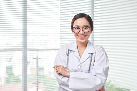 Young medical doctor woman standing on hospital background.