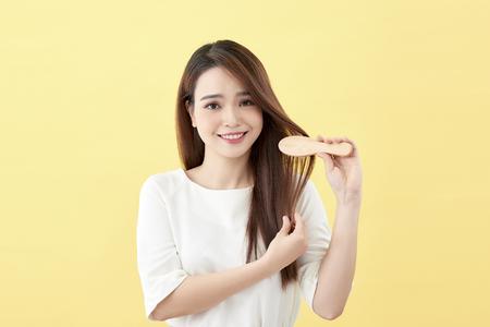 Retrato de mujer sonriente atractiva cepillando su cabello aislado en amarillo Foto de estudio