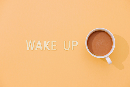 WAKE UP text with a cup of coffee with shadow on pink background. 版權商用圖片