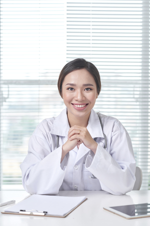 Female doctor working at office desk and smiling at camera