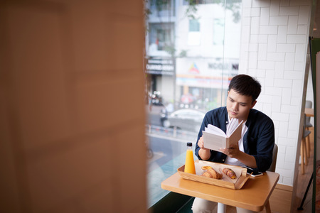 Asian man reading a book in a coffee shop. And for online shopping over the phone. - Image