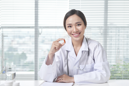 Hospital medical expert doctor shows the pill to take to her patient.