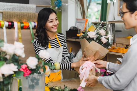 Ho Chi Minh City, Vietnam - 21 August, 2017: happy smiling florist woman making bouquet for and man or customer at flower shop Banco de Imagens