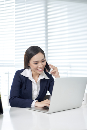 Cute young female adult with grin on phone while working on laptop computer