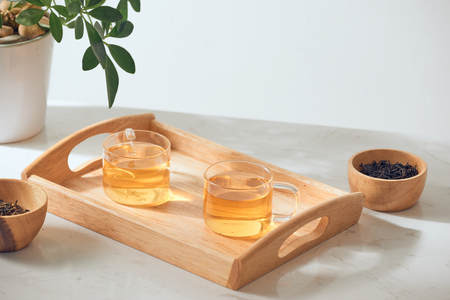 Hot tea is in the glass. Placed on a wooden tray. Stock Photo