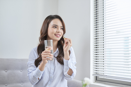 Hermosa mujer sonriente tomando píldoras de vitamina. Suplemento dietético
