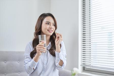 Schöne lächelnde Frau, die Vitaminpille nimmt. Nahrungsergänzungsmittel