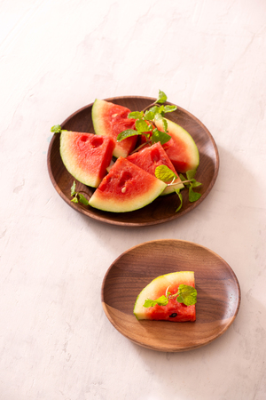 Red watermelon sliced on a wood plate on white background