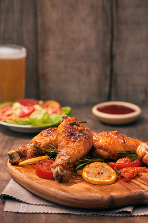 Grilled chicken legs roasted on the grill on wooden chopping board with tomato sauce in a bowl, fresh tomatoes and lettuce leaves, bitter pepper, glass mug of beer