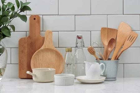 Ustensiles de cuisine rustiques simples contre un mur en bois blanc: pot en céramique rugueux avec ensemble d'ustensiles de cuisine en bois, piles de bols en céramique, cruche et plateaux en bois.