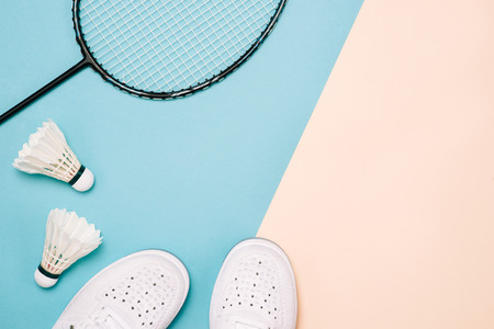 Shuttlecock and badminton racket with sport shoes on pastel color background
