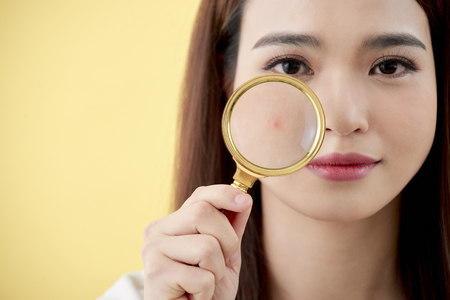 Frau mit Lupe auf gelbem Hintergrund isoliert