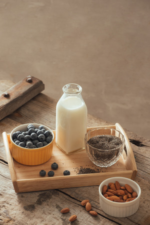 Healthy vegan breakfast. Bottled milk with chia, almond, fresh fruit and berries over wooden table background, copy space. Clean eating, weight loss, vegetarian, raw food concept Stock Photo