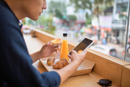 Male searches needed information on internet website via smart phone while sits at terrace cafe with juice and sweet dessert Stock Photo - 121062981