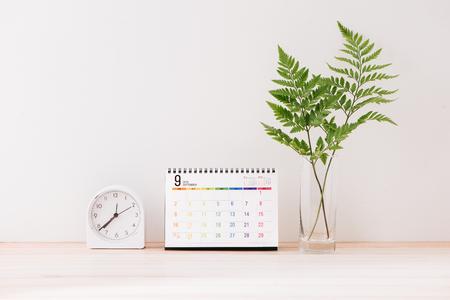 Makieta z kalendarzem z białym środkiem na tle białej ściany z budzikiem, liście w wazonie
