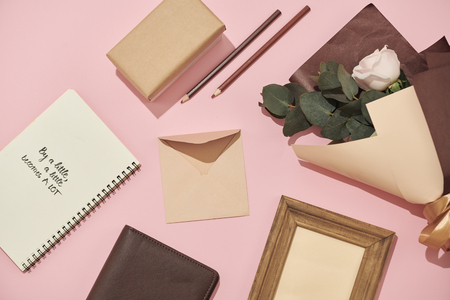 Home office workspace. Notebook with copyspace. Flat lay, magazines, social media. Top view Beauty blog concept. Woman fashion accessories on pink background 写真素材