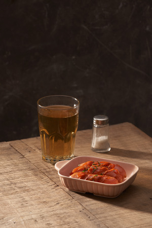 Glass of delicious beer with grilled sausages on wooden table Standard-Bild - 121063650