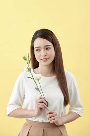 Beauty portrait of lady 20s holding white lisianthus flowers over yellow background 写真素材