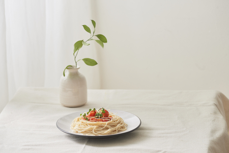 Food, spaghetti bolognese sauce in white dish and a vase of plants on a white prepared table Фото со стока - 121063663