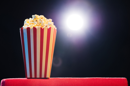 Popcorn over cinema light background, movie concept Stockfoto