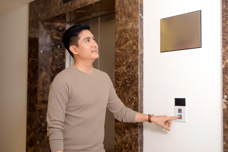 young man in casual pushing the button to call an elevator in building