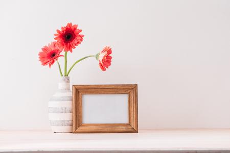 Cadre de paysage blanc simulé avec un vase de gerbera à côté du cadre, superposez votre citation, promotion, titre ou design, idéal pour les petites entreprises, les blogueurs lifestyle et les campagnes sur les réseaux sociaux Banque d'images