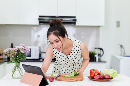 woman using tablet while making a healthy salad at the kitchen Standard-Bild