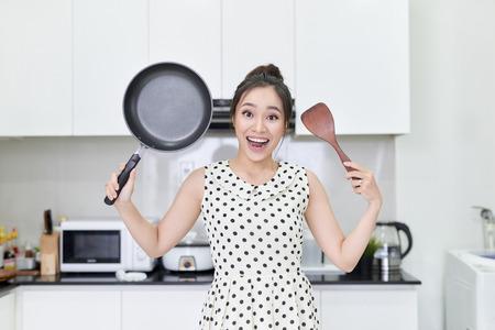 Jeune femme montrant une casserole et une spatule Banque d'images