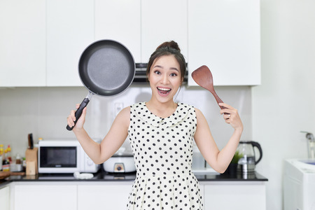 Young woman showing a pan and a spatula