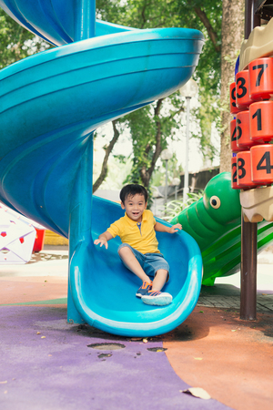 Child play on playground concept. Asian boy child play and smile on slider in playground park in school on morning