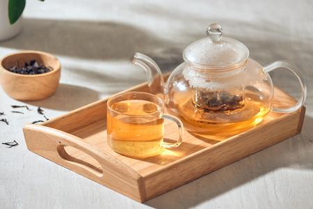 Thé dans une tasse et une théière transparentes sur un fond en bois