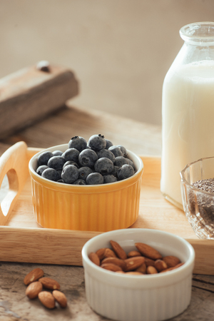 Healthy vegan breakfast. Bottled milk with chia, almond, fresh fruit and berries over wooden table background, copy space. Clean eating, weight loss, vegetarian, raw food concept Banco de Imagens