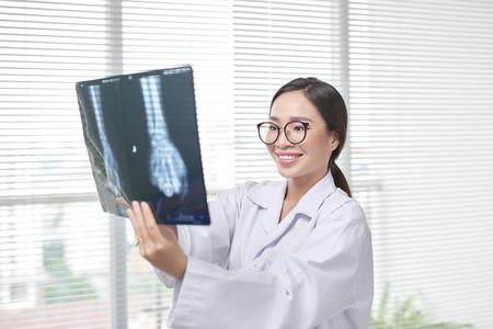 Woman in scrubs examining X-rays