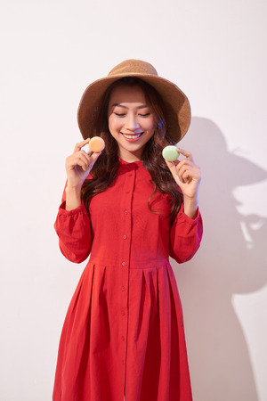 Sweet woman. Happy girl plays with macaroons. Stock Photo