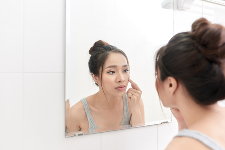 Skin care. Woman applying skin cream on her face in front of mirror