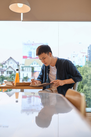 Handsome young designer writes creative graphic notes and making sketch in notebook while sitting at wooden table in coffee interior. Thoughtful man writing new successful ideas for blog article