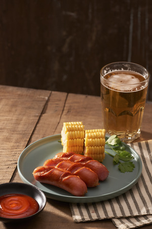 Beer and grilled sausages on wooden background Stockfoto