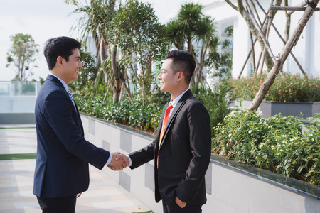two handsome businessmen greeting each other in the street