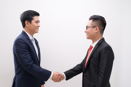 Side view of two smiling young businessmen shaking hands in white background